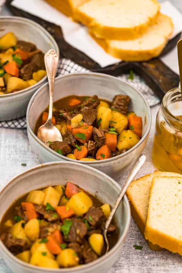 beef stew in bowls next to bread