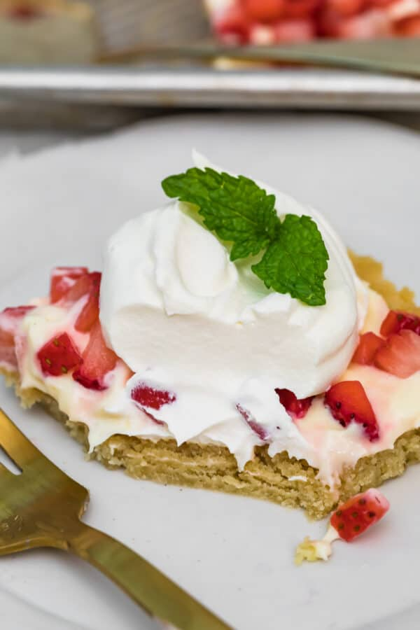 sugar cookie bar topped with strawberries and whipped cream