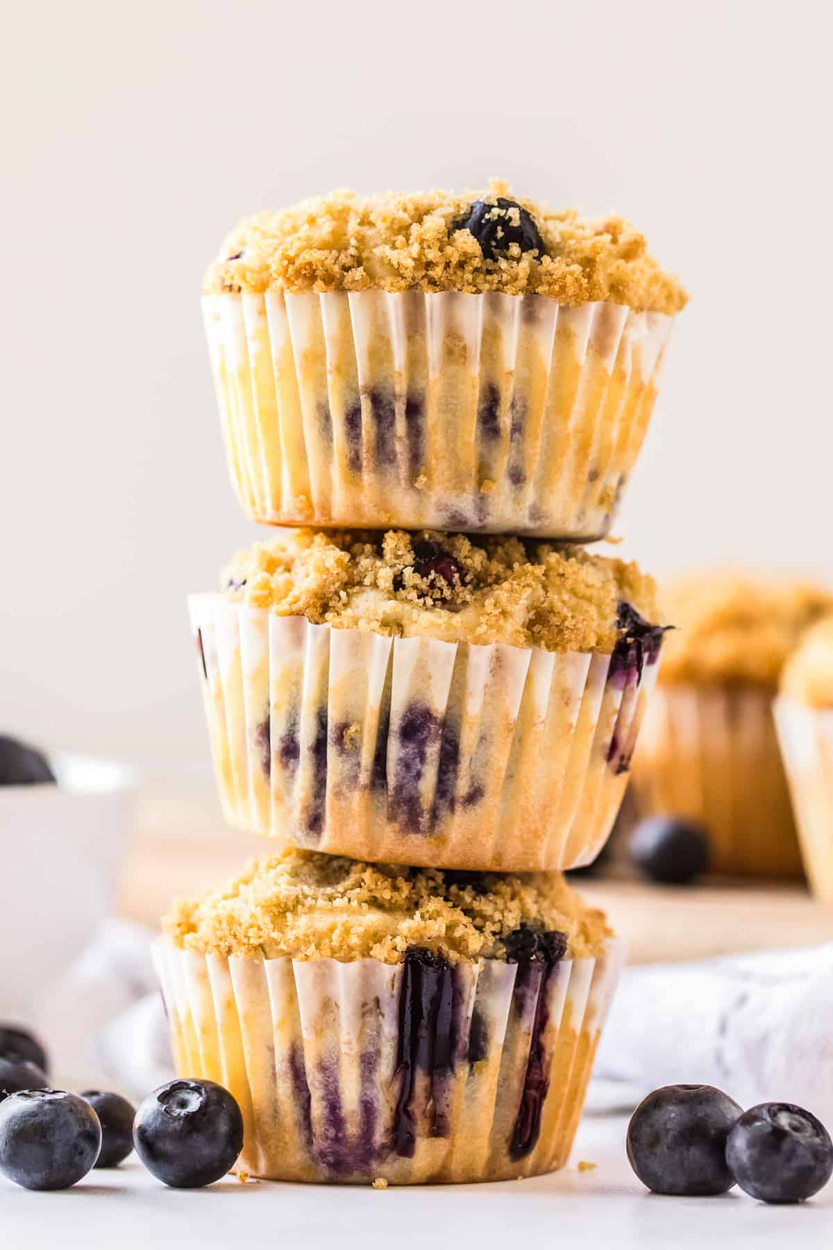 three muffins stacked with blueberries