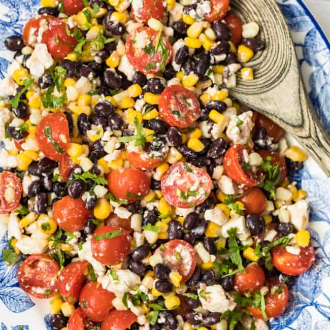 corn salad with tomatoes on blue platter