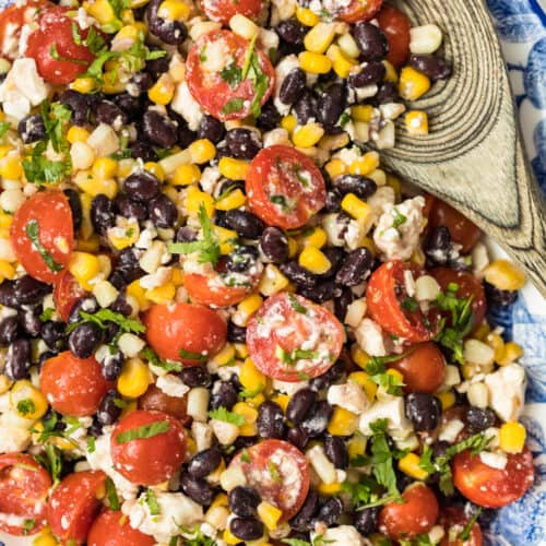 tomato corn salad on platter with wooden spoon