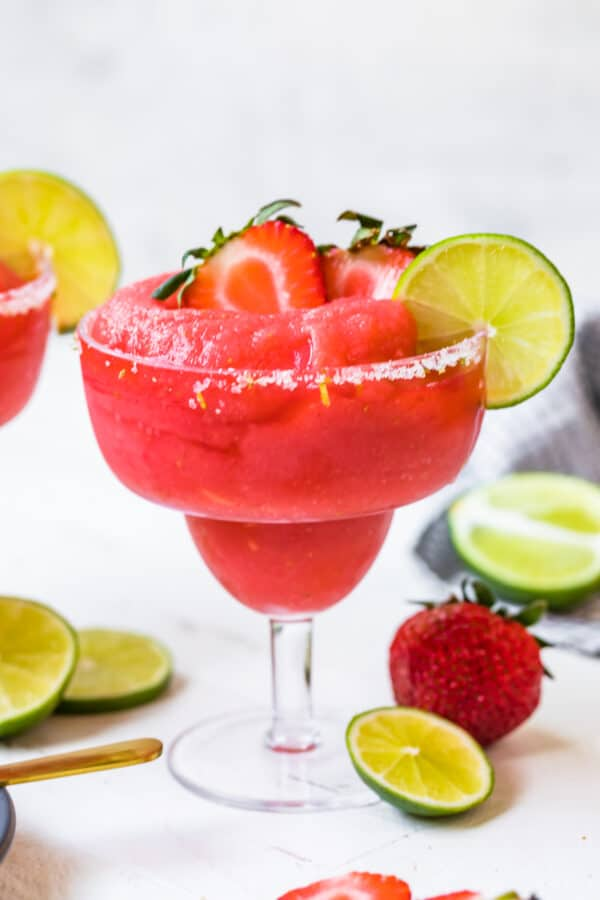 frozen strawberry margaritas garnished with fruit and salt