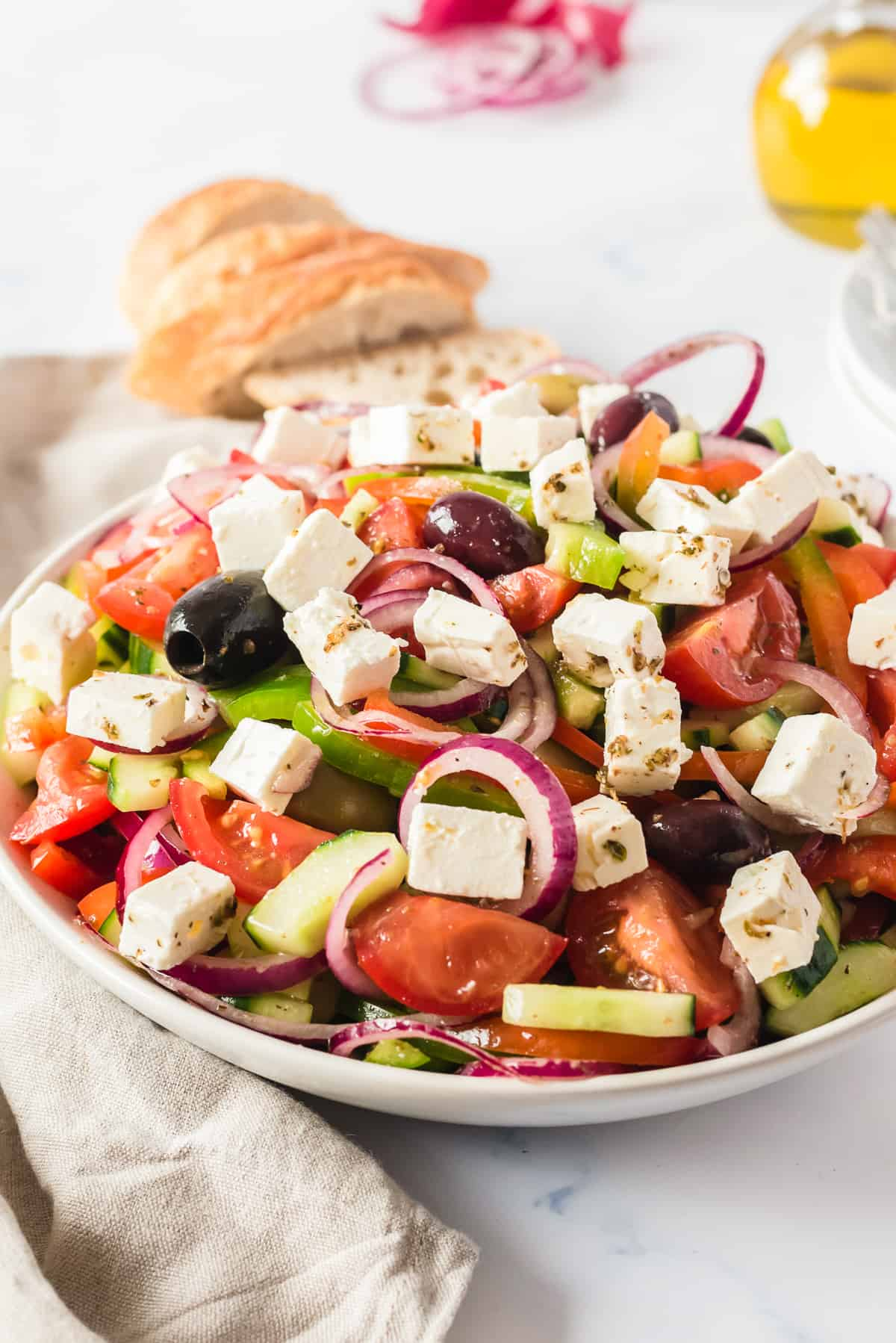 side shot of salad in white bowl with bread