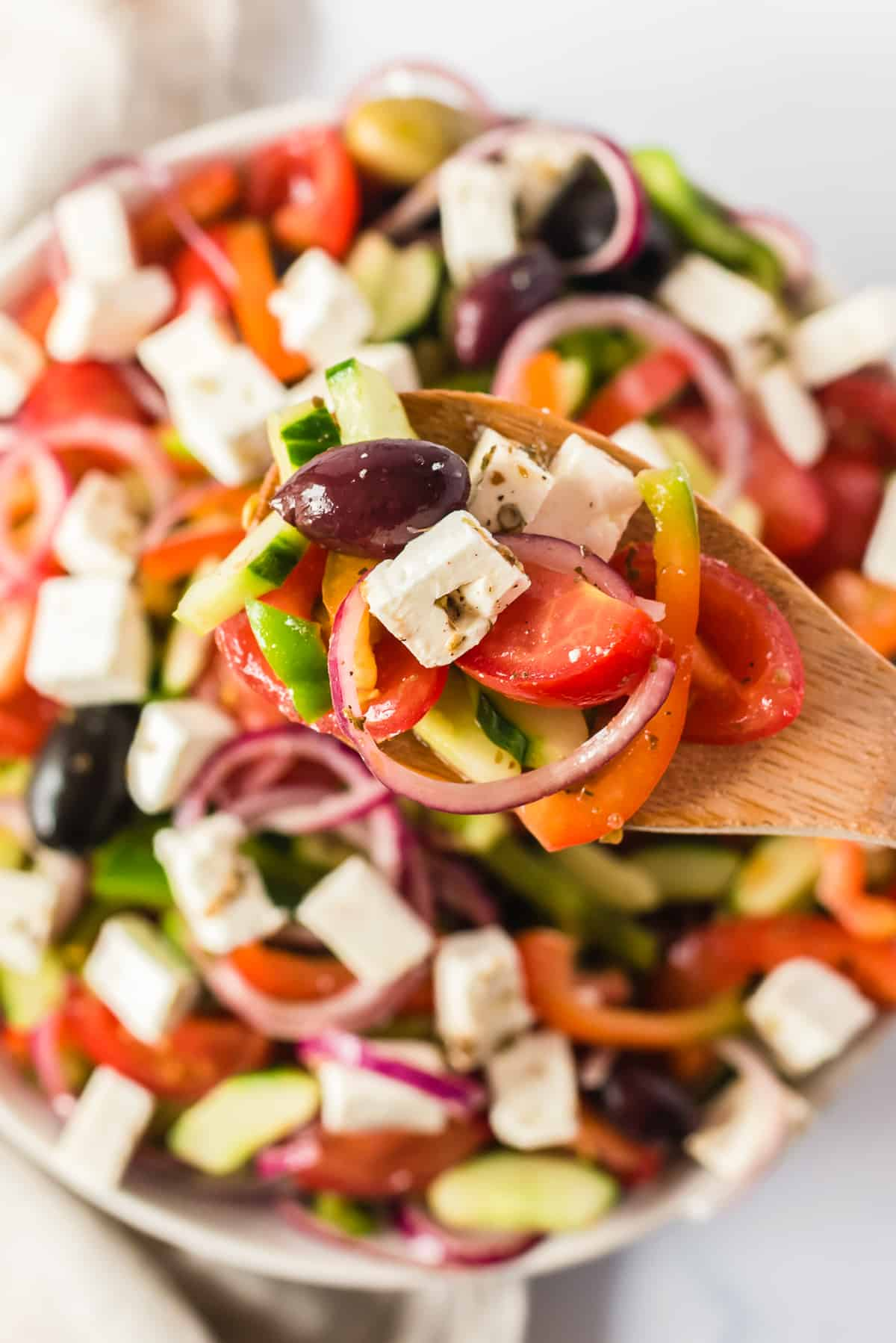 spoon lifting up traditional greek salad ingredients