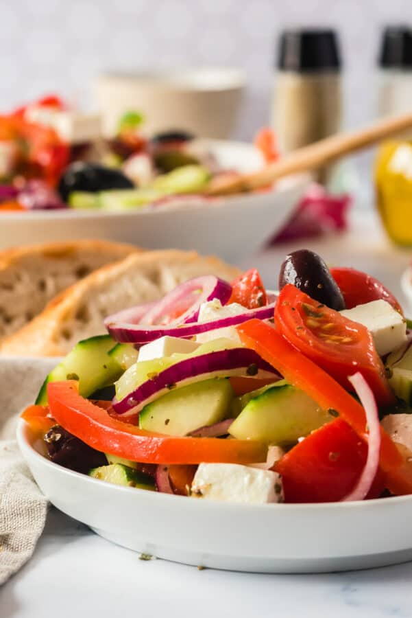 side shote of salad in white bowl with bread