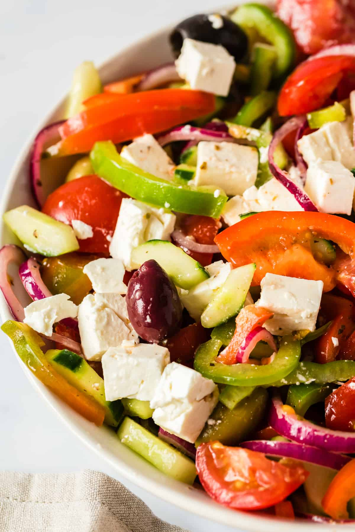tossed greek salad in white bowl