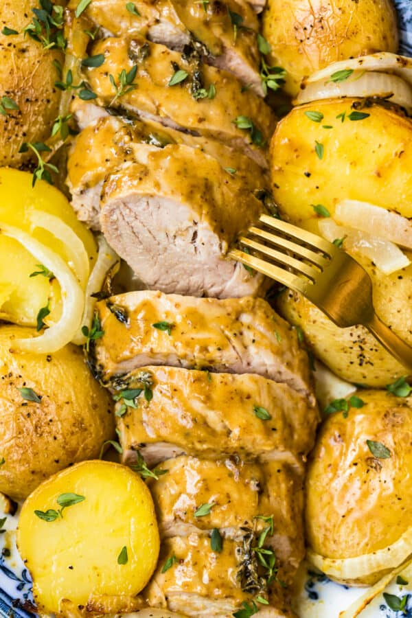 up close image of pork tenderloin with honey mustard sauce and potatoes