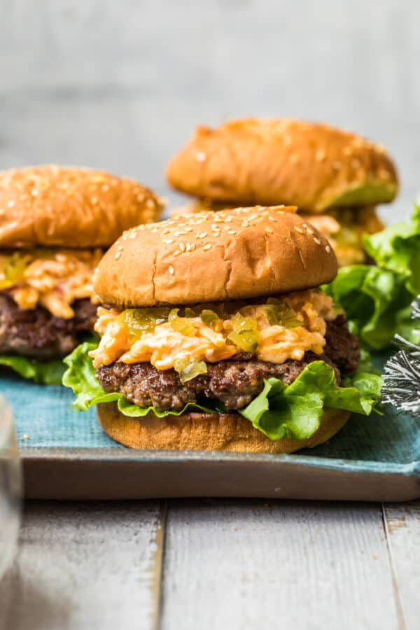 side shot of pimento cheeseburgers on blue platter