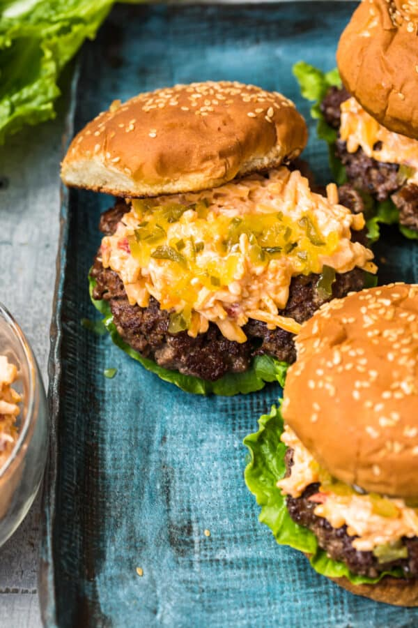 burger topped with pimento cheese and relish with bun half on