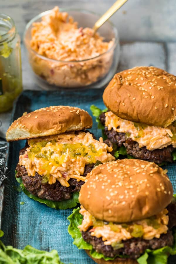 pimento cheeseburgers on blue platter next to relish and pimento cheese
