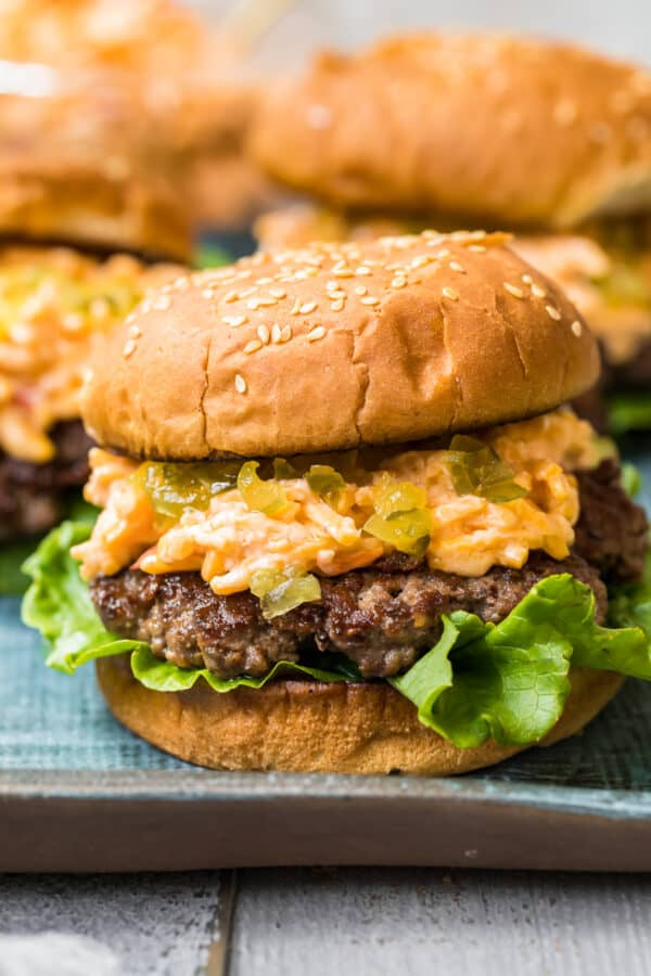 up close image of burger topped with pimento cheese and relish