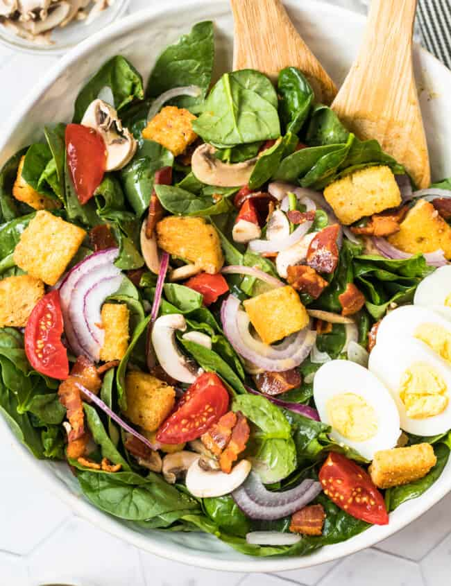 spinach bacon salad with spinach salad dressing in white bowl