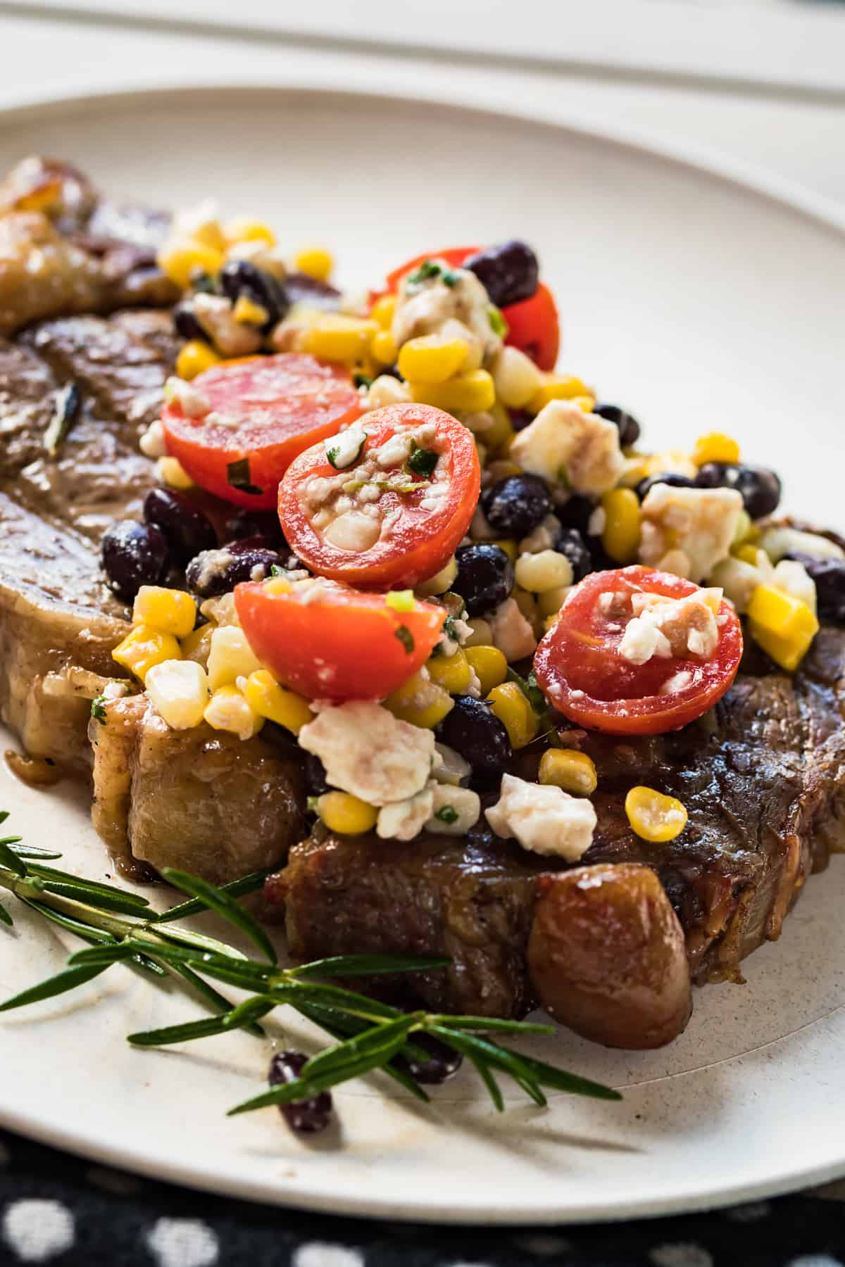 grilled ribeye topped with tomatoes and corn