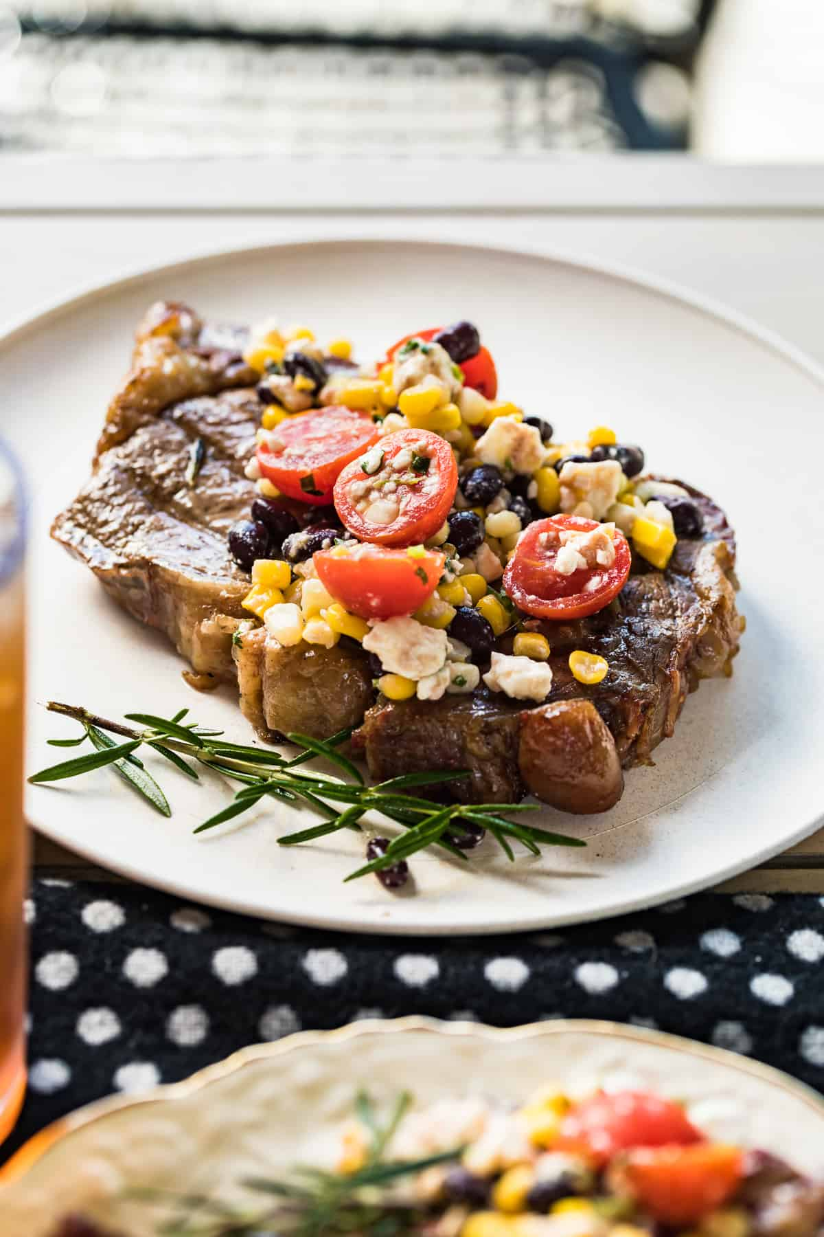 grilled ribeye topped with tomatoes and corn on plate