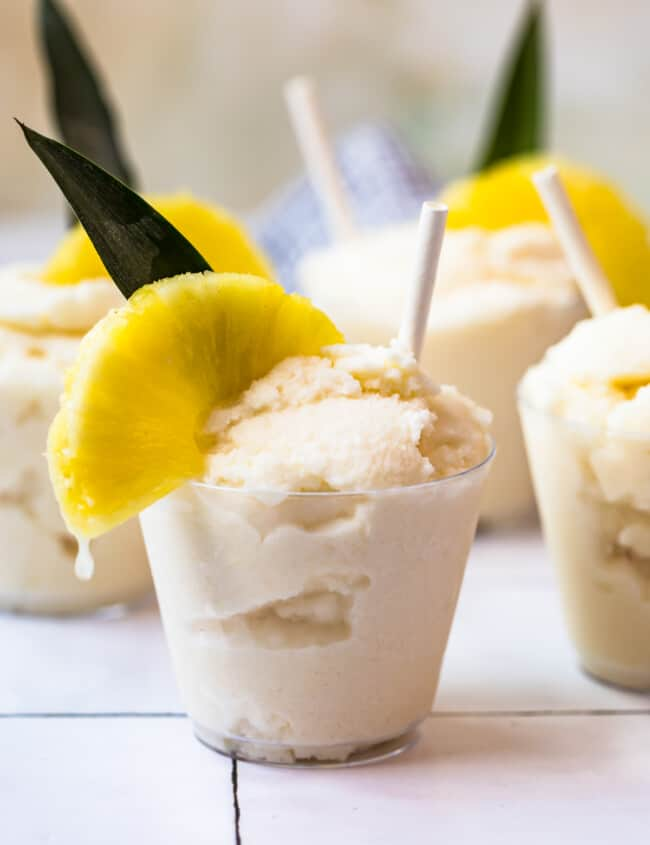 creamy frozen pina coladas in glasses garnished