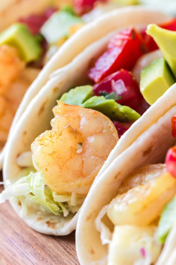 up close image of shrimp tacos with pineapple slaw