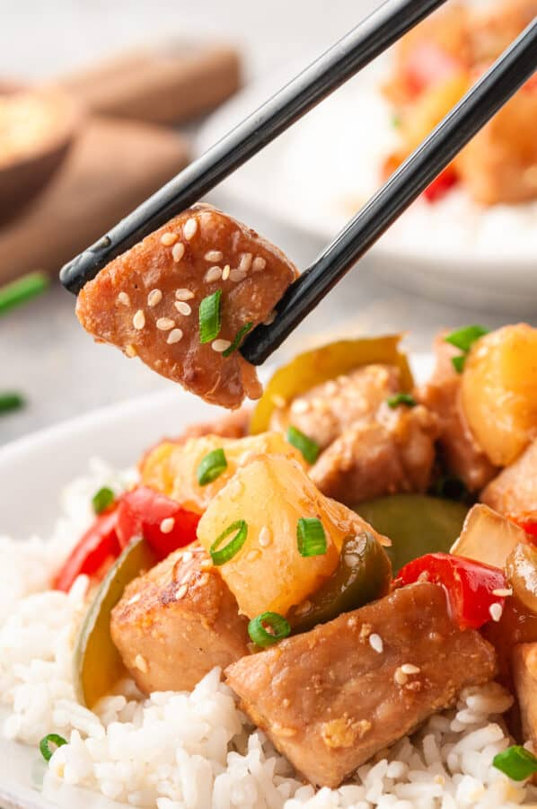 lifting up piece of sweet and sour pork