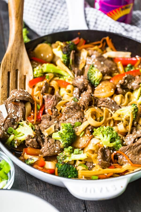 side image of beef lo mein with wooden spoon