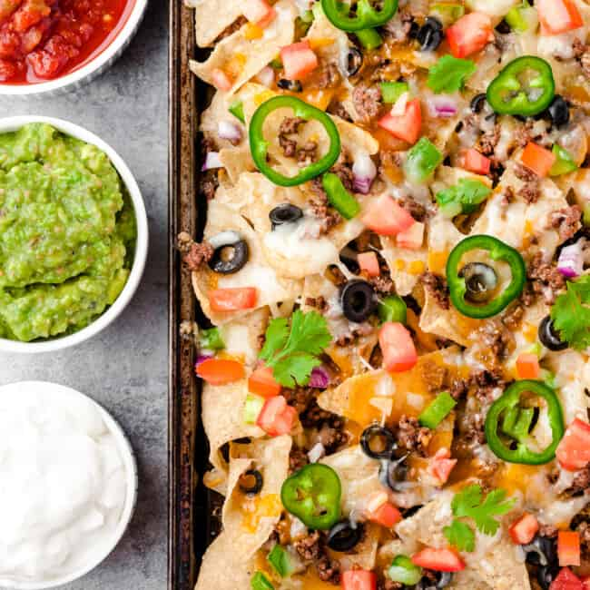 baked beef nachos next to sour cream, salsa, and guacamole
