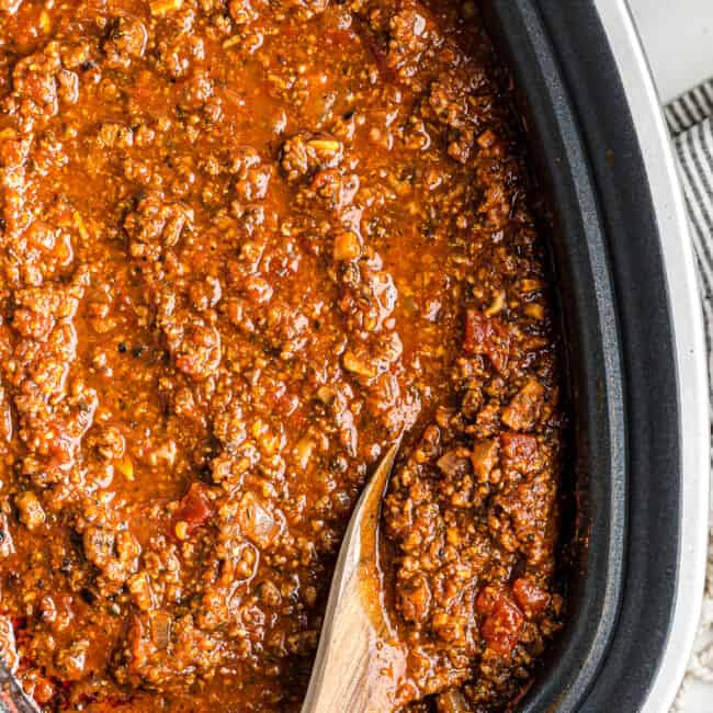 wooden spoon in spaghetti sauce in slow cooker