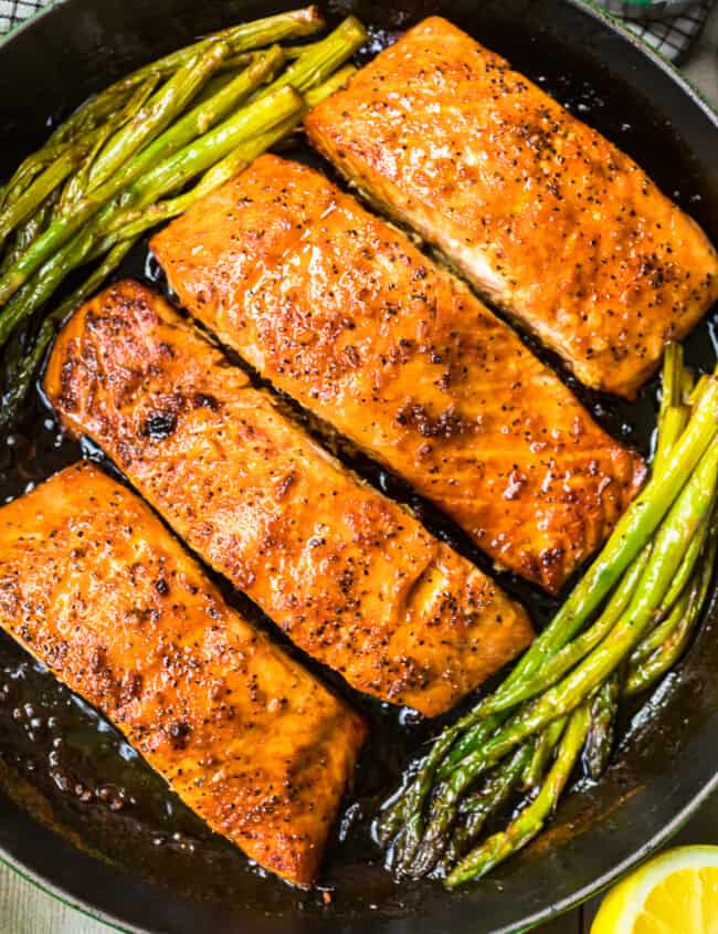 up close honey garlic salmon with asparagus in skillet