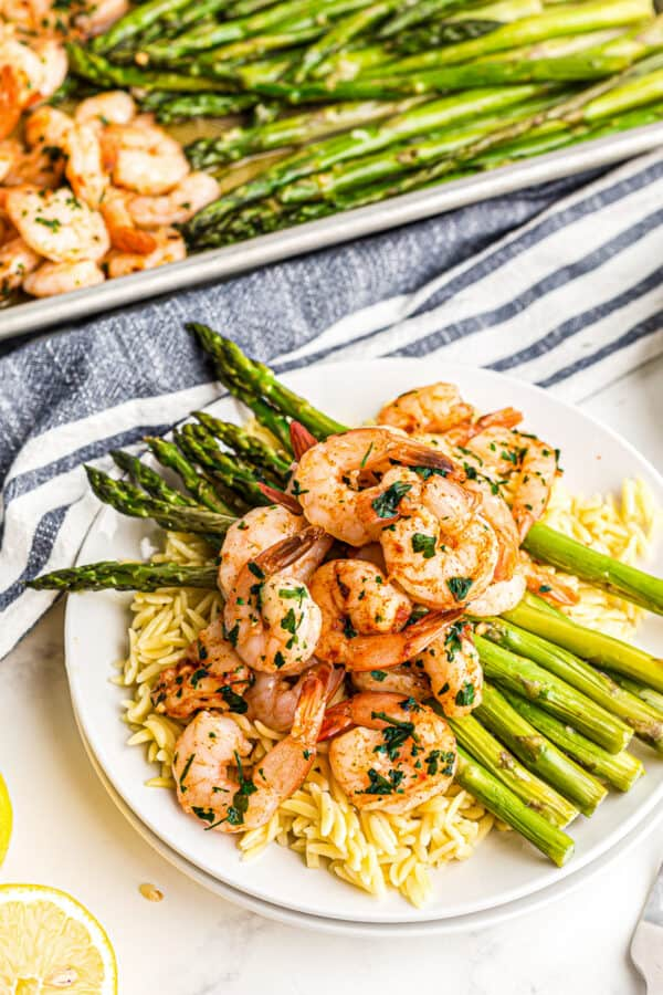 shrimp and asparagus over rice on plate