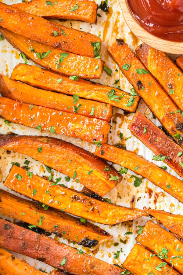 up close image of baked sweet potato fries on sheet pan