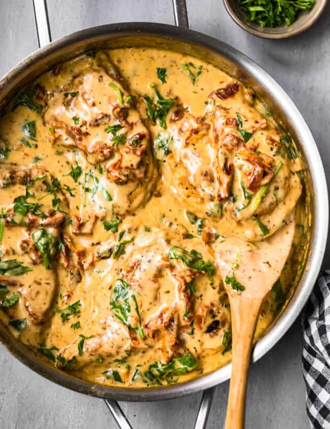 side shot of tuscan chicken in cream sauce with wooden spoon