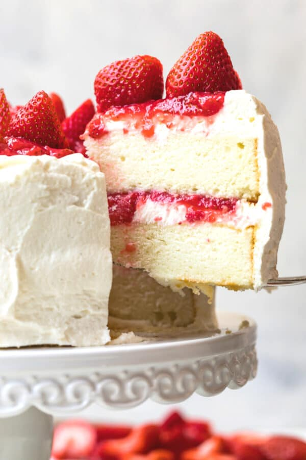 lifting slice of white layer cake with strawberry filling
