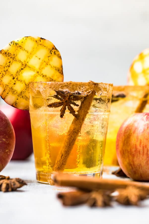 straight on photo of apple cider margarita with grilled apple and cinnamon