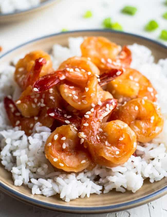 honey sesame shrimp over rice on brown plate