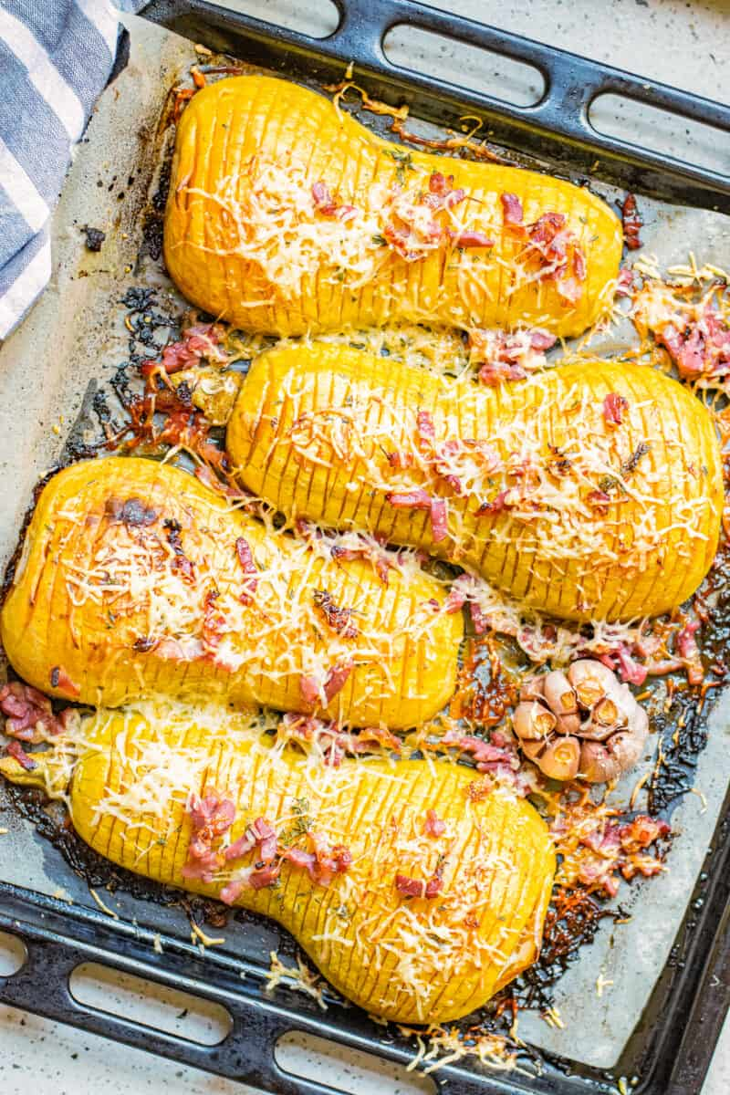 roasted butternut squash hasselback with bacon and cheese on baking sheet.
