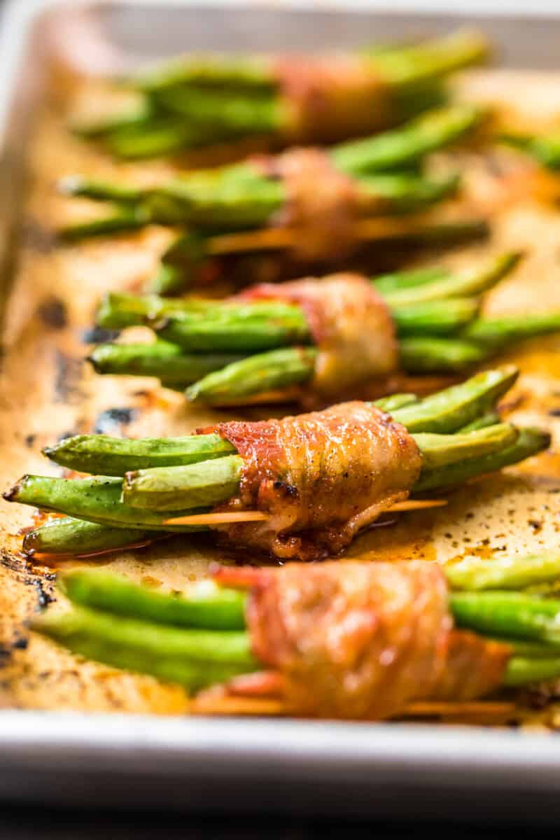 green beans wrapped in bacon on baking sheet