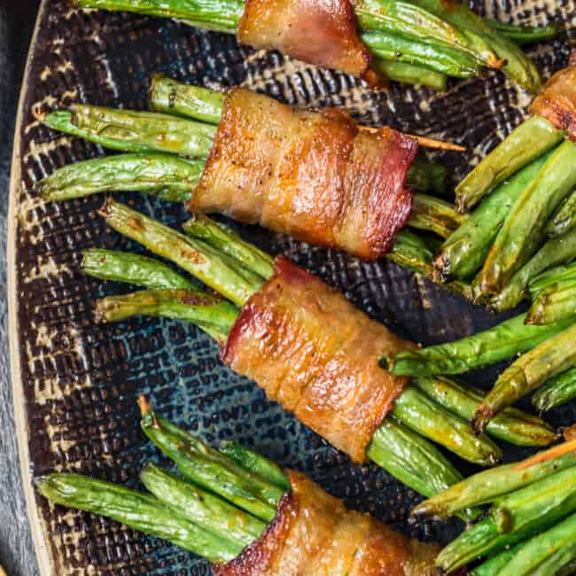 black platter with green beans wrapped in bacon