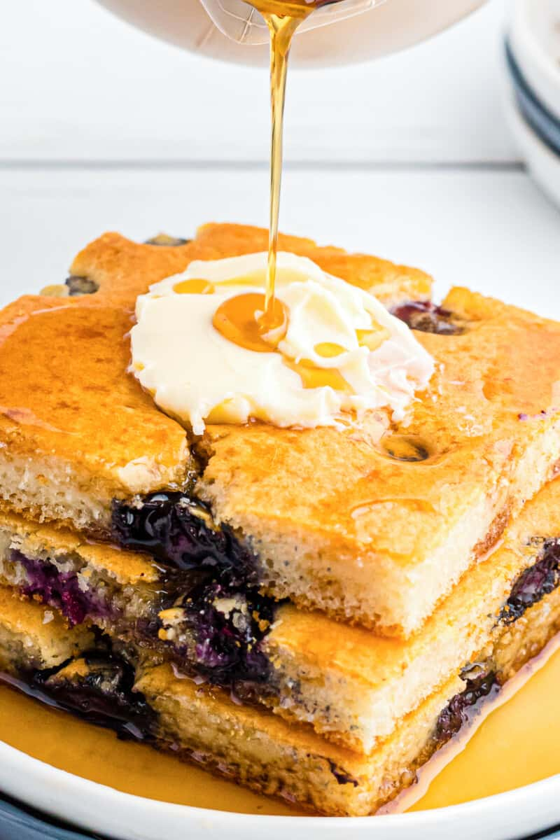 drizzling syrup on sheet pan blueberry pancakes