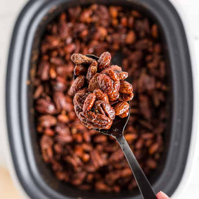 lifting up spoonful of crockpot candied nuts