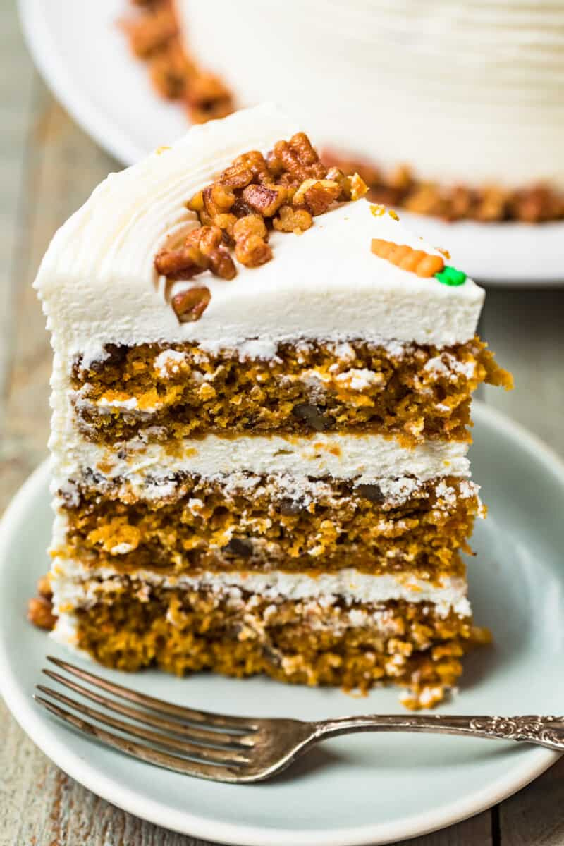 slice of carrot cake with three layers and cream cheese icing