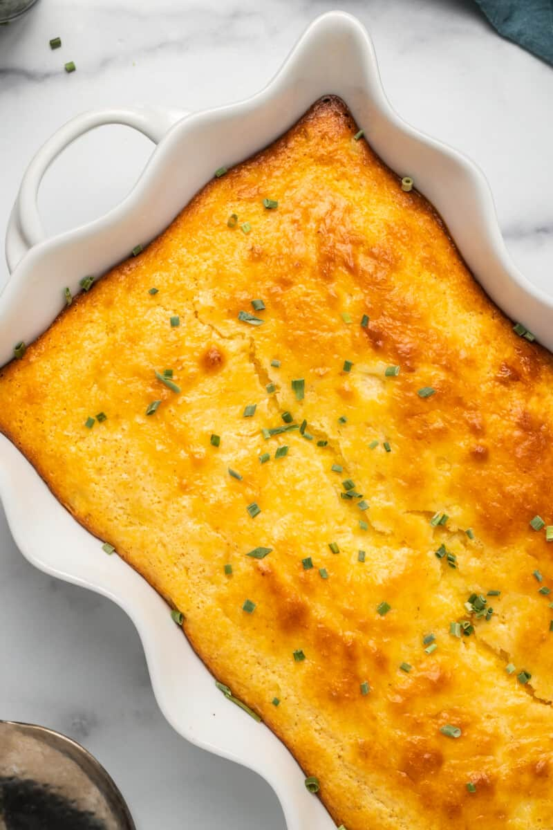 side image of loaded cornbread casserole garnished with chives
