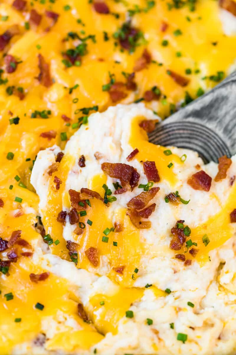 spoon digging into loaded mashed potato casserole