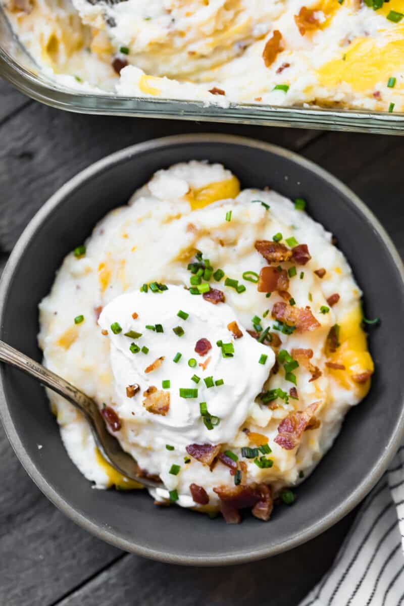 bowl of mashed potato casserole topped with sour cream