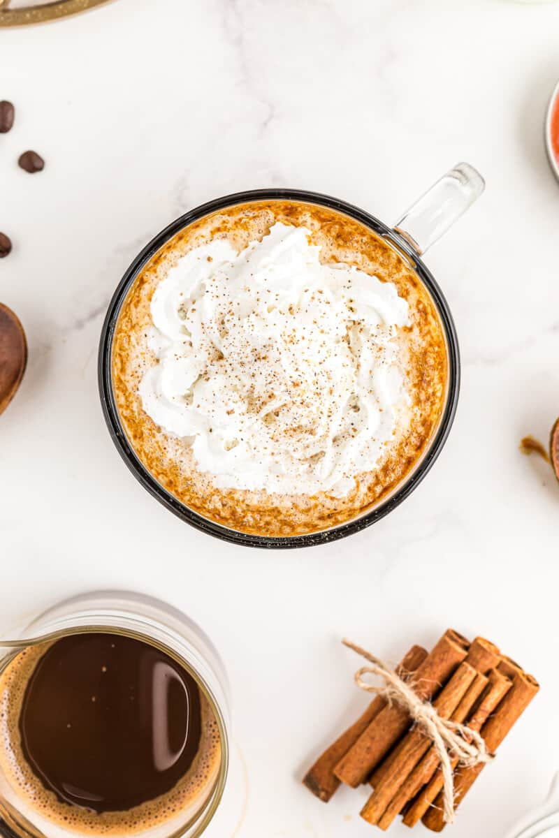overhead image of pumpkin spice lattes topped with whipped cream