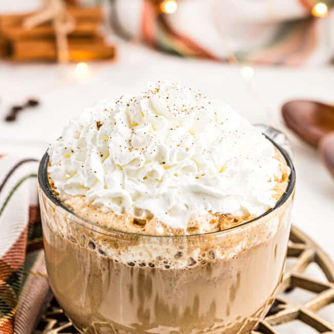 large clear mug with pumpkin spice latte topped with whipped cream