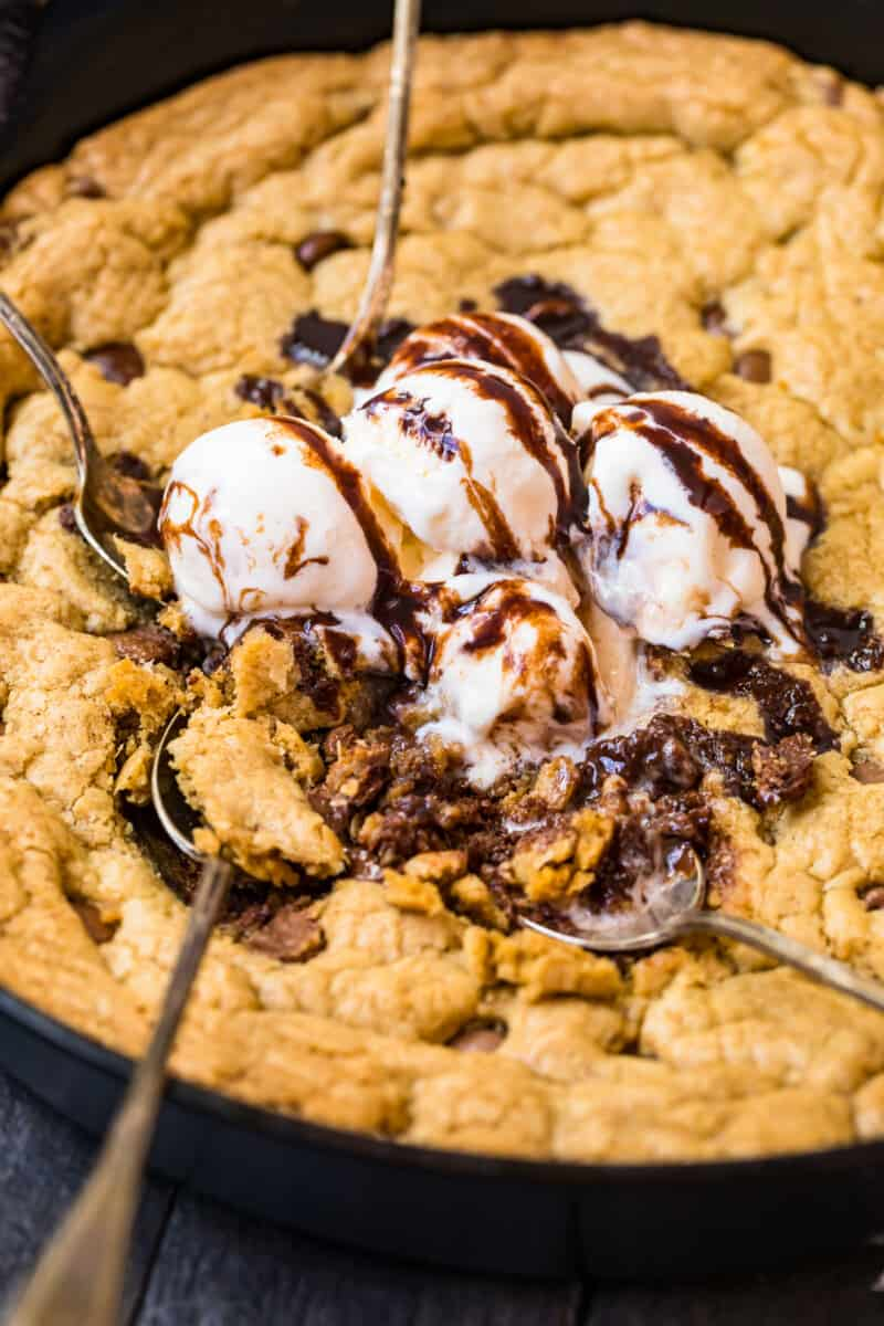digging into skillet chocolate chip cookie with ice cream and syrup