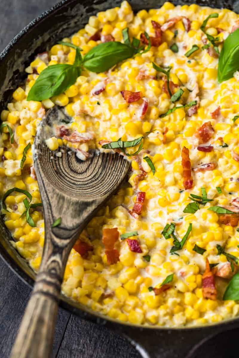 wooden spoon in skillet creamed corn with bacon