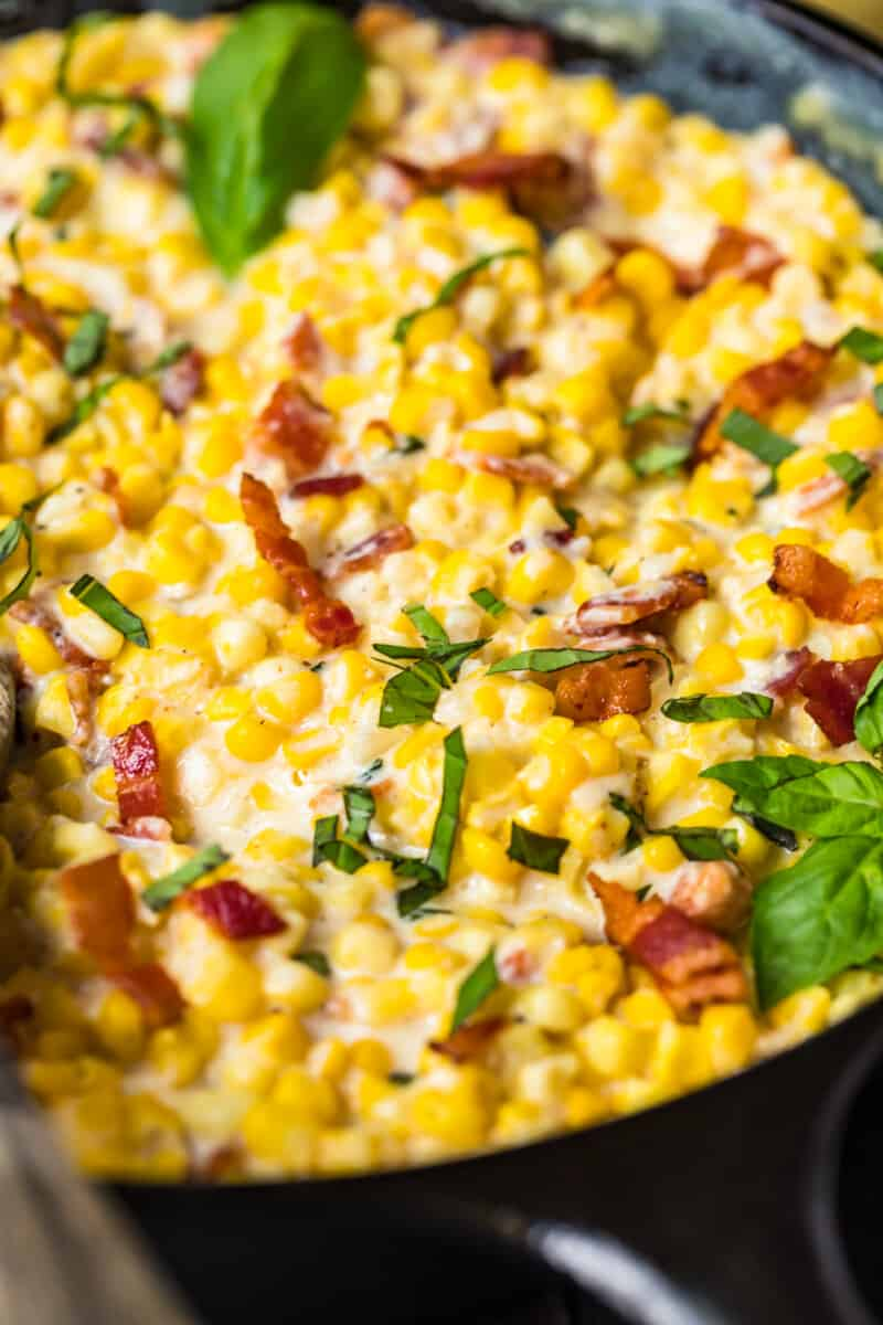 up close image of creamed corn with bacon and basil