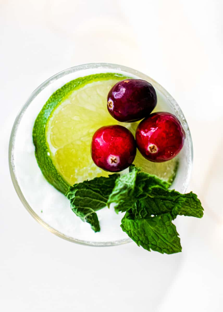 overhead image of coconut mojito with cranberries, mint, and lime