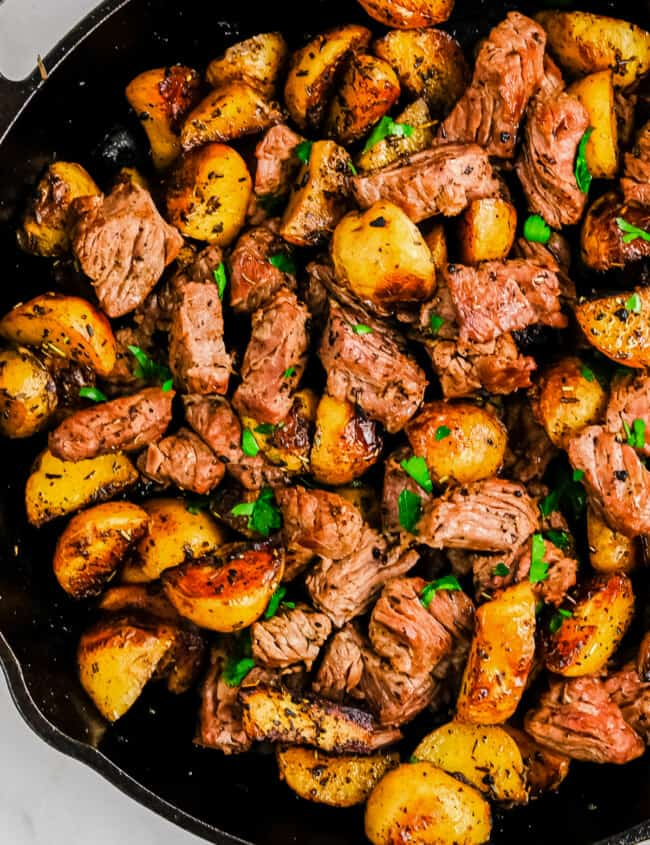 garlic steak bites with potatoes in skillet
