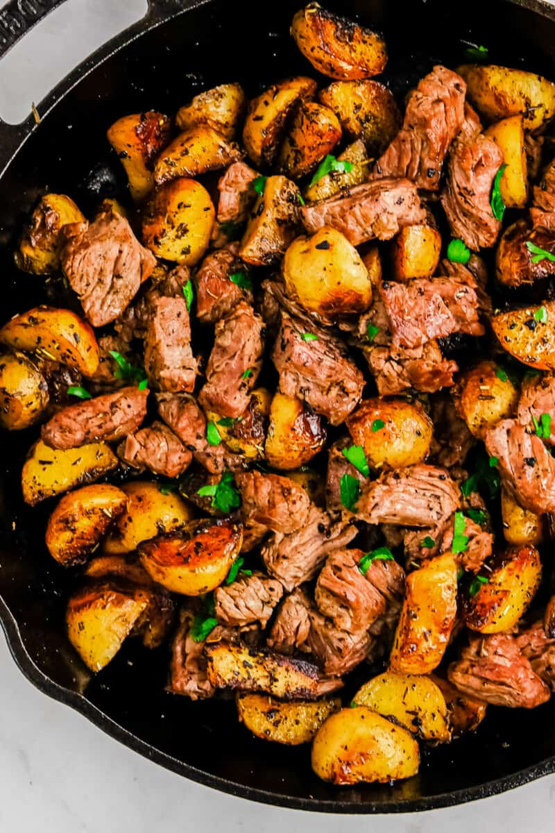 garlic steak bites with potatoes in skillet