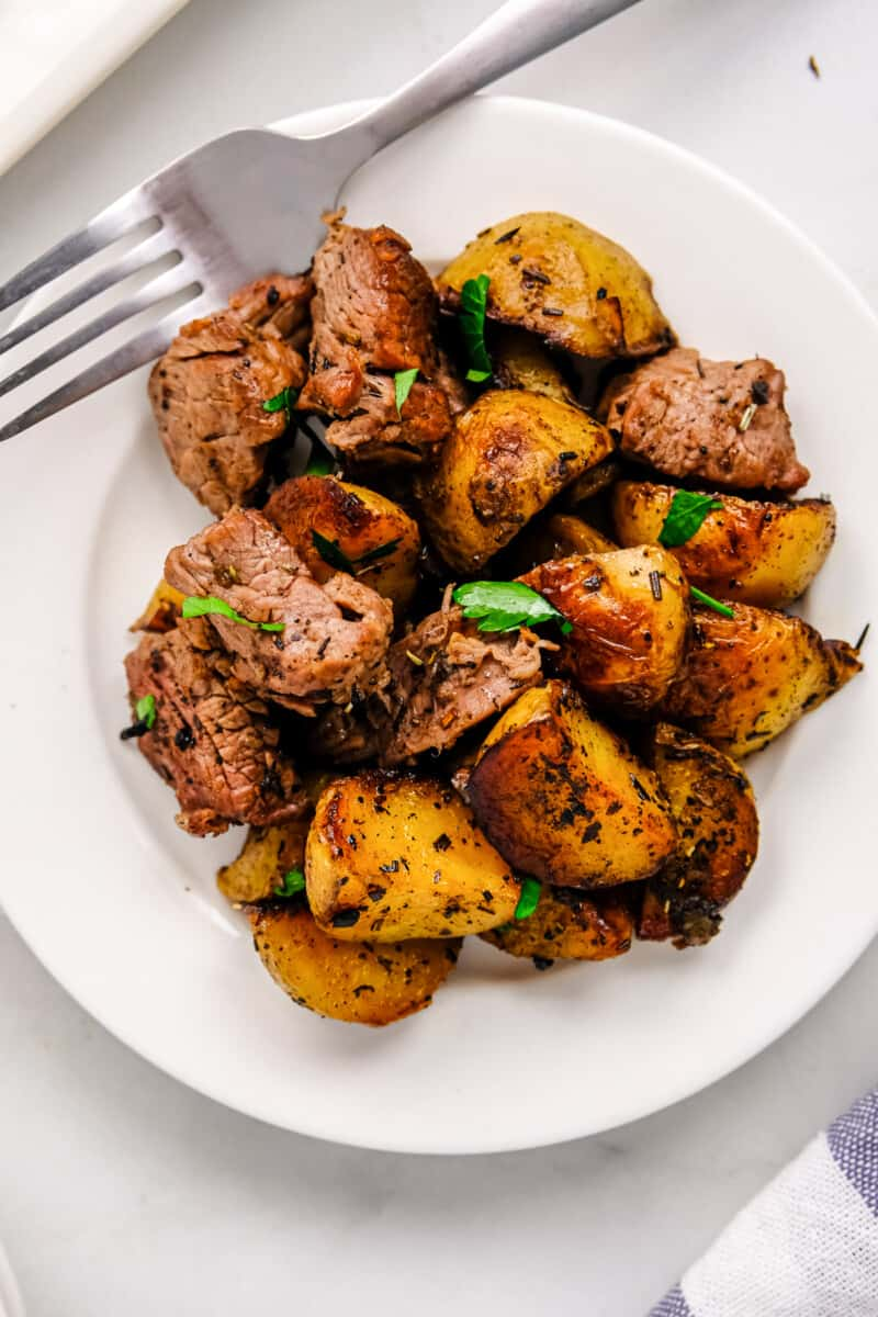 garlic steak bites with potatoes on white plate