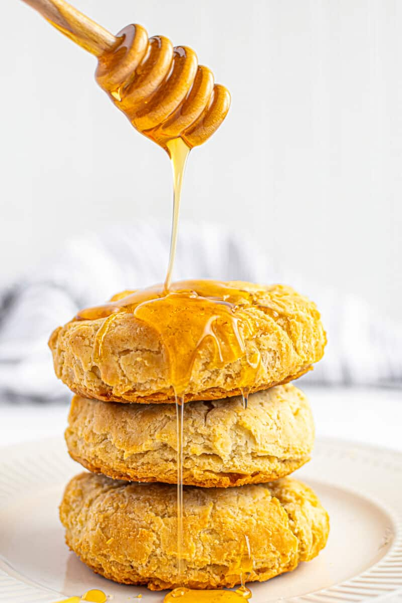 pouring honey over gluten free biscuits